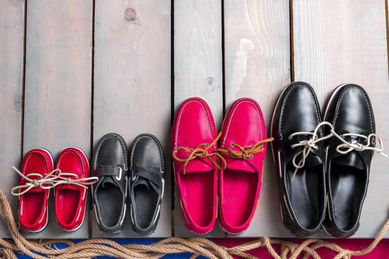 Family boat shoes on wooden background, Four pair of red and black boat shoes